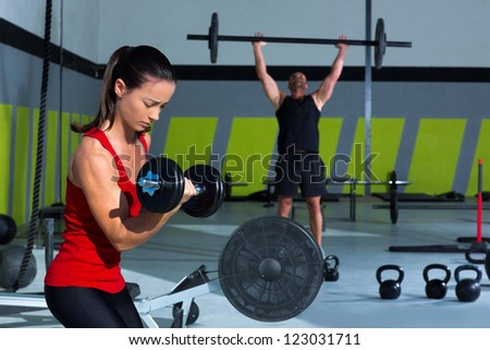 girl dumbbell and man weight lifting bar workout  at  gym - stock photo