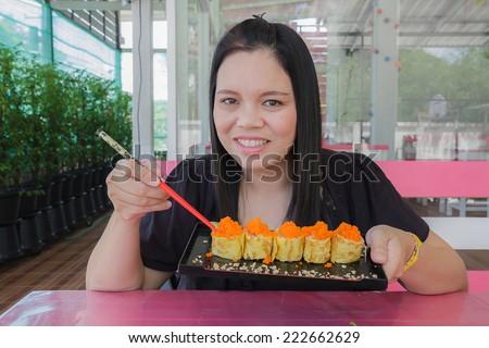 Girl eat sushi egg in the restaurant - stock photo