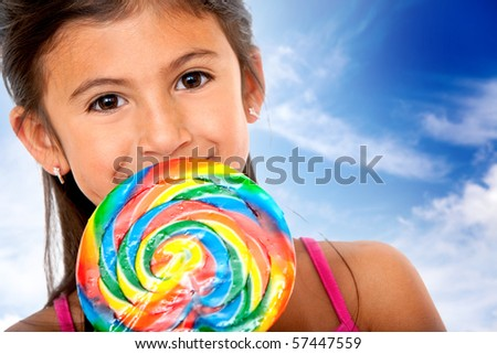 Girl eating a colorful candy with the sky on the background - stock photo