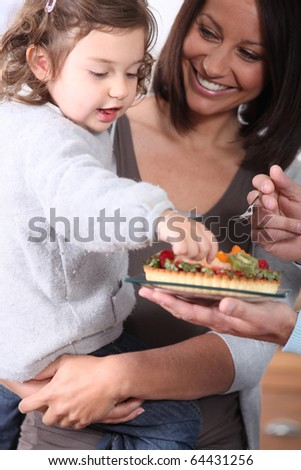 Girl eating a fruit pie with his mother