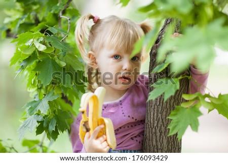 girl eating banana on the tree - stock photo