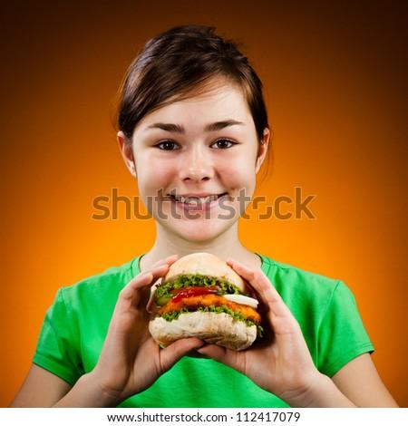 Girl eating big sandwich - stock photo