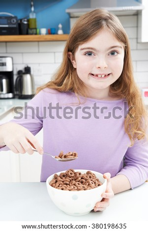Girl Eating Bowl Of Sugary Breakfast Cereal In Kitchen - stock photo