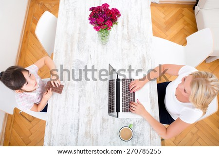 Girl eating chocolate at the table at home while the mother is working.  - stock photo