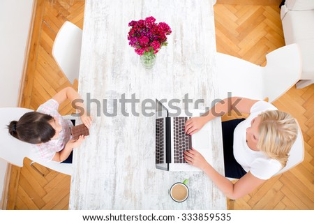 Girl eating chocolate at the table at home while the mother is working.