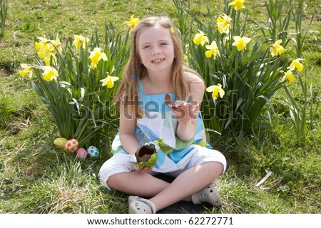 Girl Eating Chocolate Egg On Easter Egg Hunt In Daffodil Field