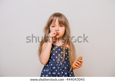Girl eating cookies. little girl in polka-dot dress. Girl eats sweet. baby hungry. Girl eats snack - stock photo