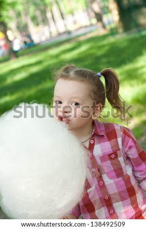 Girl eating cotton candy in a park - stock photo