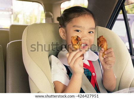 Girl Eating Fried Chicken on car - stock photo