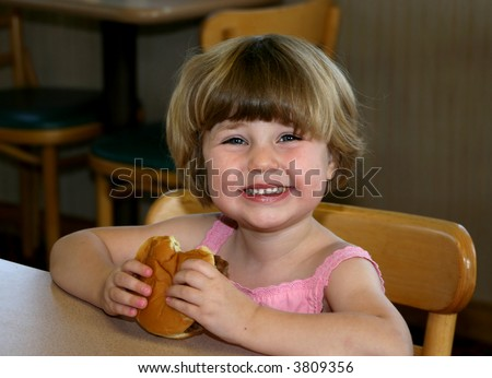 Girl eating hamburger in fast-food restaurant - stock photo