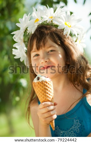 girl eating ice cream and looking at camera - stock photo