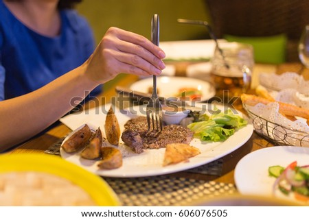 Girl eating meat with salad in a restaurant