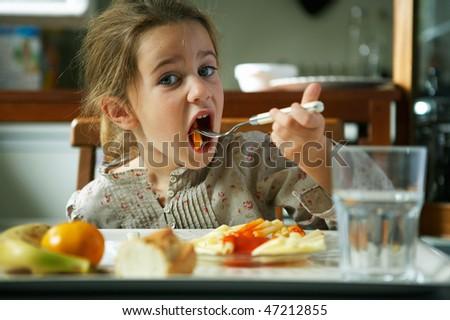 girl eating pasta - stock photo