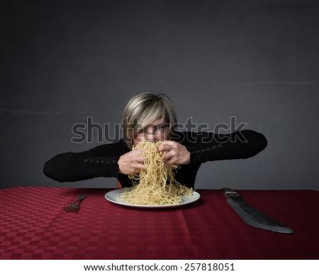 girl eating pasta like an animal - stock photo