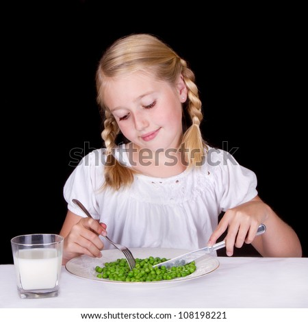 Girl eating peas with milk isolated on black background - stock photo