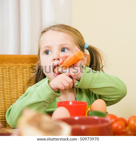 Girl eating suspiciously healthy looking food - vegetables - stock photo