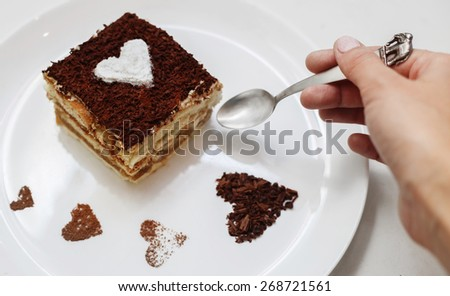 Girl eating tiramisu cake with heart - stock photo