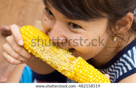 Girl eats corn