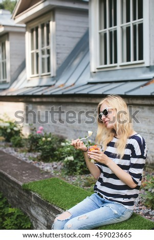 Girl eats fruit mix sitting in the street near the building