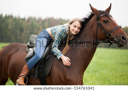 girl embraces a horse - stock photo