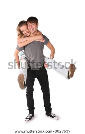 girl embraces boy from behind, he holds her on the hands for the legs on the the white - stock photo