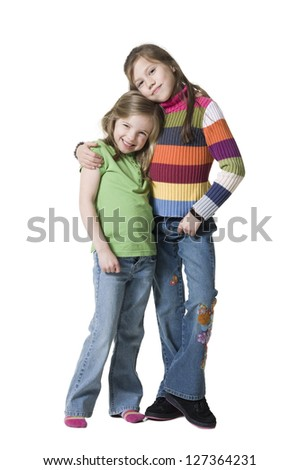 Girl embracing her little sister over white background