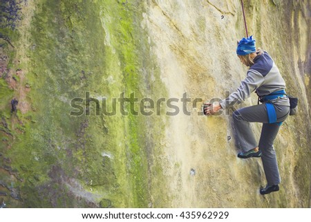 Girl engaged in rock climbing on the cliffs.  - stock photo