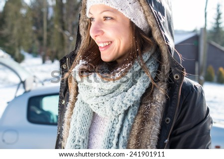 Girl enjoy snow and sunshine in winter by car - stock photo