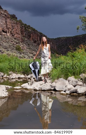 Girl enjoying a day by the river, prepared for rain