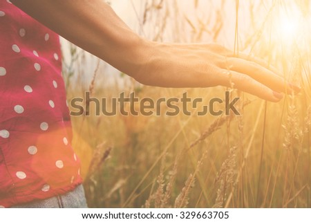 Girl enjoying in a countryside scenic. Shallow depth of field on the hand. - stock photo
