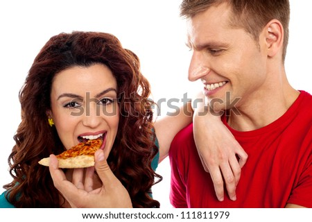 Girl enjoying pizza piece shared by her boyfriend. Great love couple - stock photo