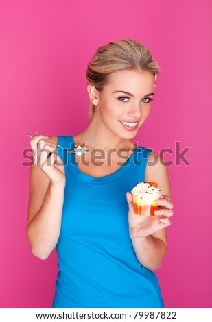 girl enjoying pudding on pink background - stock photo
