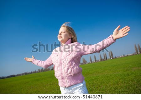 Girl enjoying the sun under blue sky background