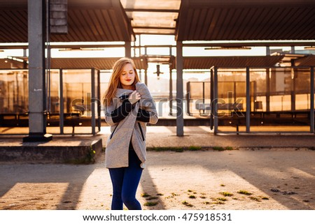 Girl envelopes herself in grey coat while standing in the lights of evening sun