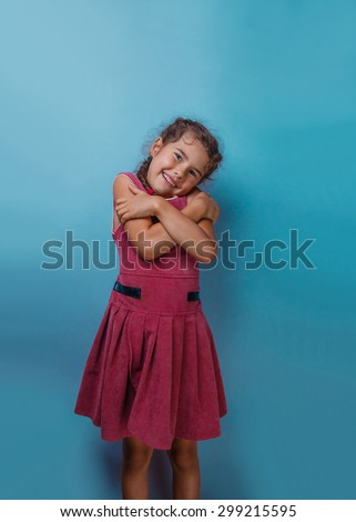 Girl European appearance decade hugging herself on a blue background - stock photo