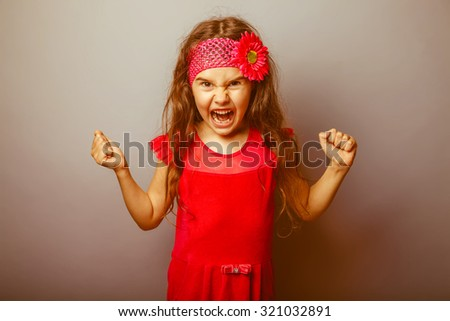 Girl European appearance haired child of seven in red bright dress on a gray background shouts, anger, anger retro - stock photo