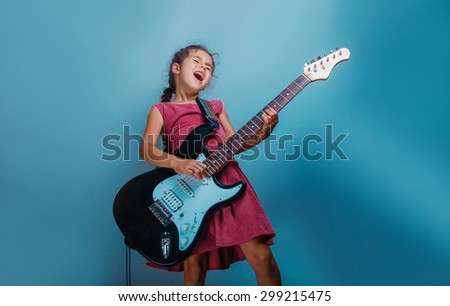 Girl European appearance ten years playing guitar on a blue  background - stock photo