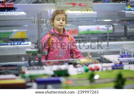 Girl examines exposure in mobile exhibition and lecture complex of Russian Railways - stock photo