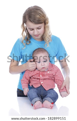 Girl examines the forehead of a baby  - stock photo