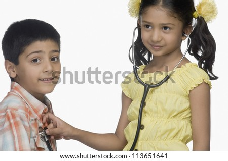 Girl examining a boy with a stethoscope - stock photo