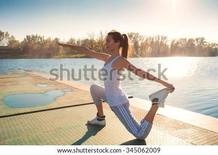 girl exercise by the lake sunny  autumn day, full body shot - stock photo