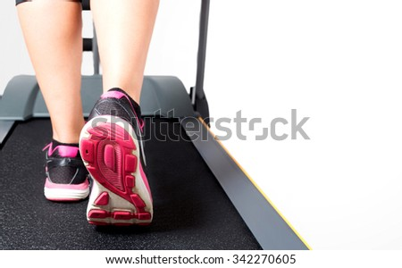 Girl exercise on treadmill on pink black sport shoes with white space - stock photo
