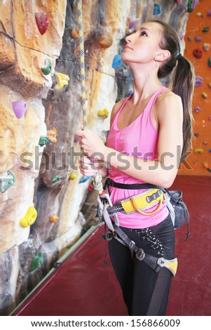 Girl exercises on indoor rock climber - stock photo