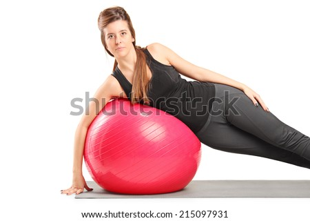 Girl exercising with pilates ball on exercise mat isolated on white background
