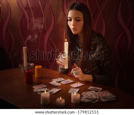 girl extinguishes candles after divination - stock photo