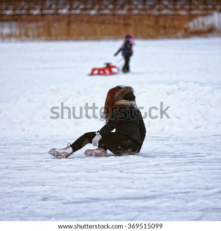 Girl falling down while ice skating on winter rink. Skating involves any sports or recreational activity which consists of traveling on surfaces or on ice using skates. Selective focus - stock photo