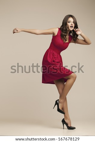 girl falls on the long heels. Beautiful girl in red dress - stock photo
