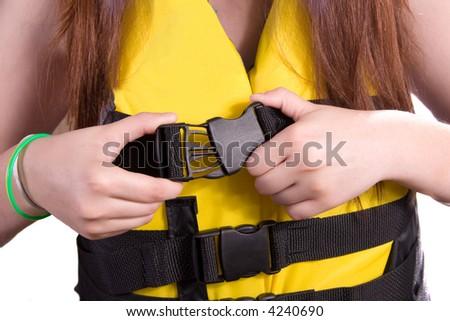 Girl Fastening buckle on life jacket/ski vest - stock photo
