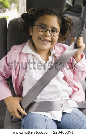 Girl fastening seatbelt in backseat of car - stock photo