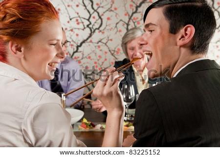 Girl feeding a guy with chopsticks - stock photo